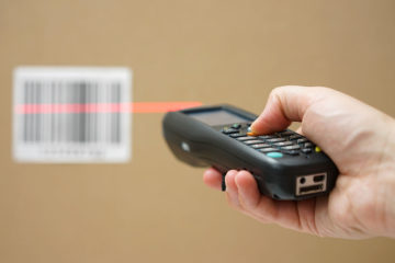 closeup of hand holding bar code scanner and scanning code on cardboard box