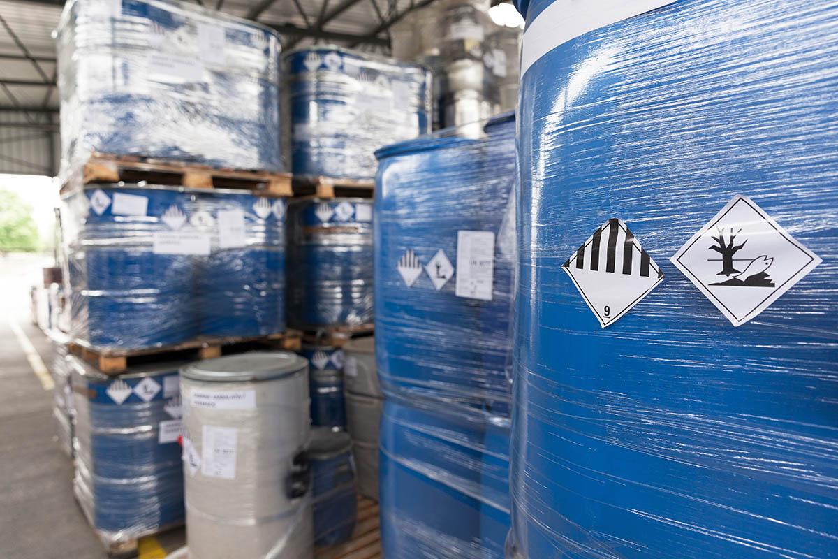 Waste barrels with hazard warning symbols in the warehouse